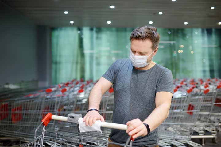 Man wearing a mask to protect from coronavirus wiping down shopping cart