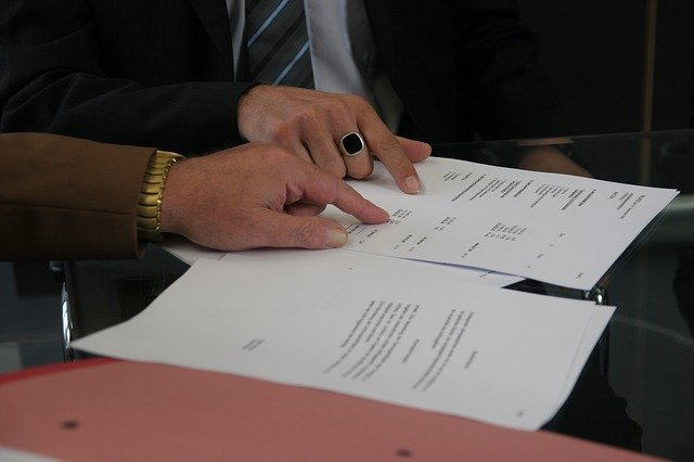hands of two people pointing a provisions of a contract