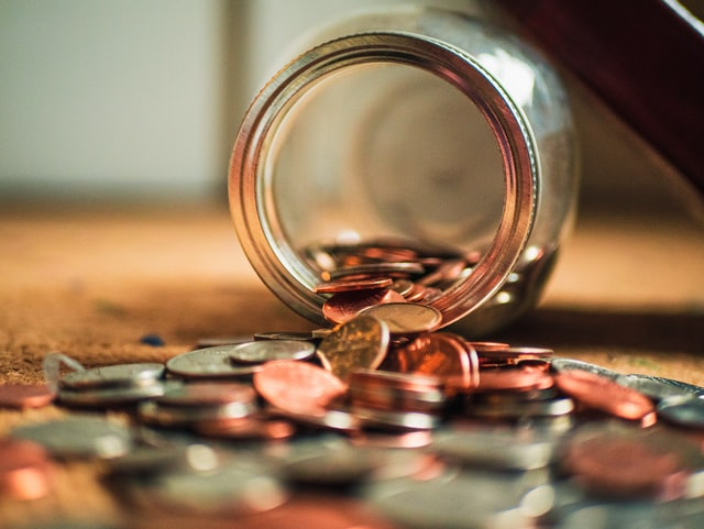coins spilling from mason jar