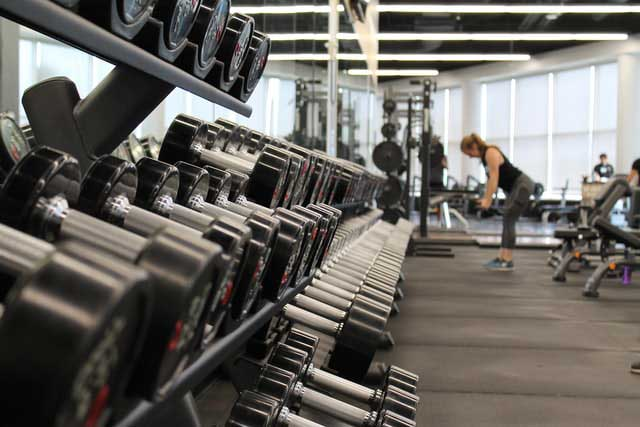woman-lifting-weights-fitness-center-covid19-business-closures