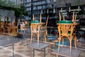 restaurant chairs stacke on tables in a closed storefront