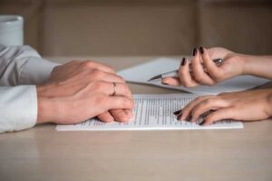 hands of man and woman signing papers