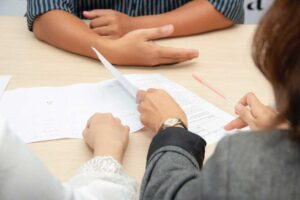 hands of three people shown reviewing documents